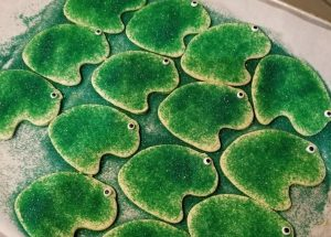 Frog-shaped sugar cookies, topped with green-colored sugar, with googly eyes. These are based on Catapult Greater Pittsburgh's Logo