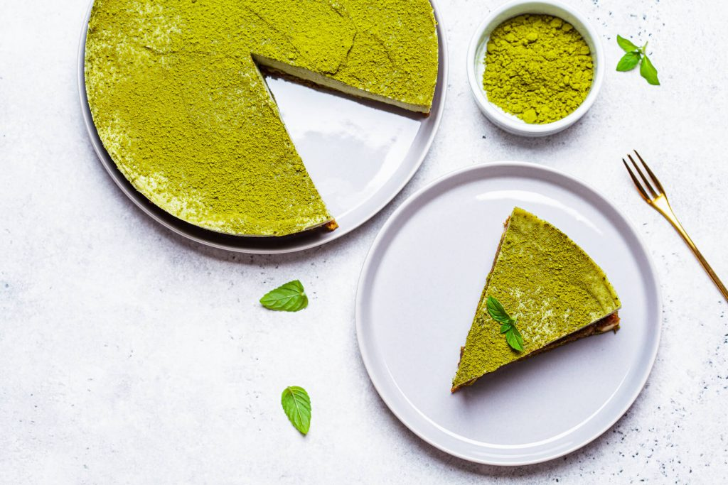A cheesecake topped with matcha garnished with green leaves, with a bowl of matcha powder beside it. One slice is taken out and set on a plate.