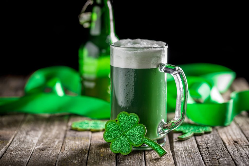 A glass of green beer with a shamrock decoration on it, various green Saint Patrick's Day themed items in the background.