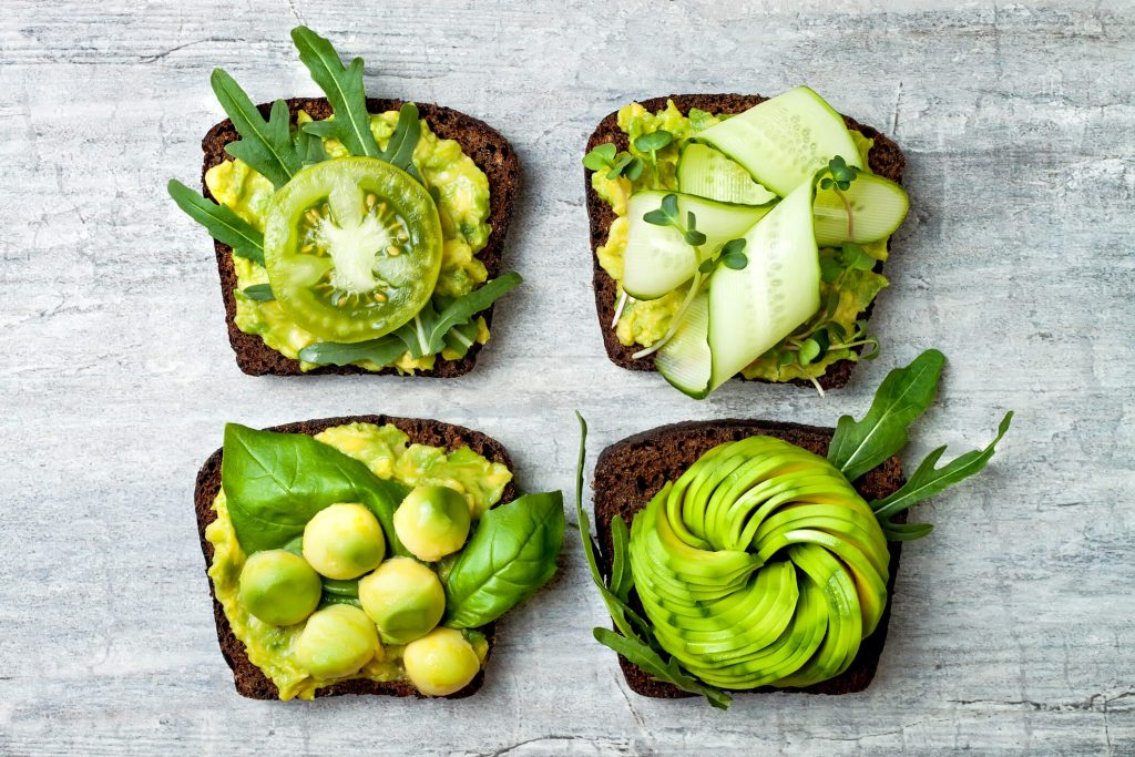 Avocado toast top-down view with various green toppings