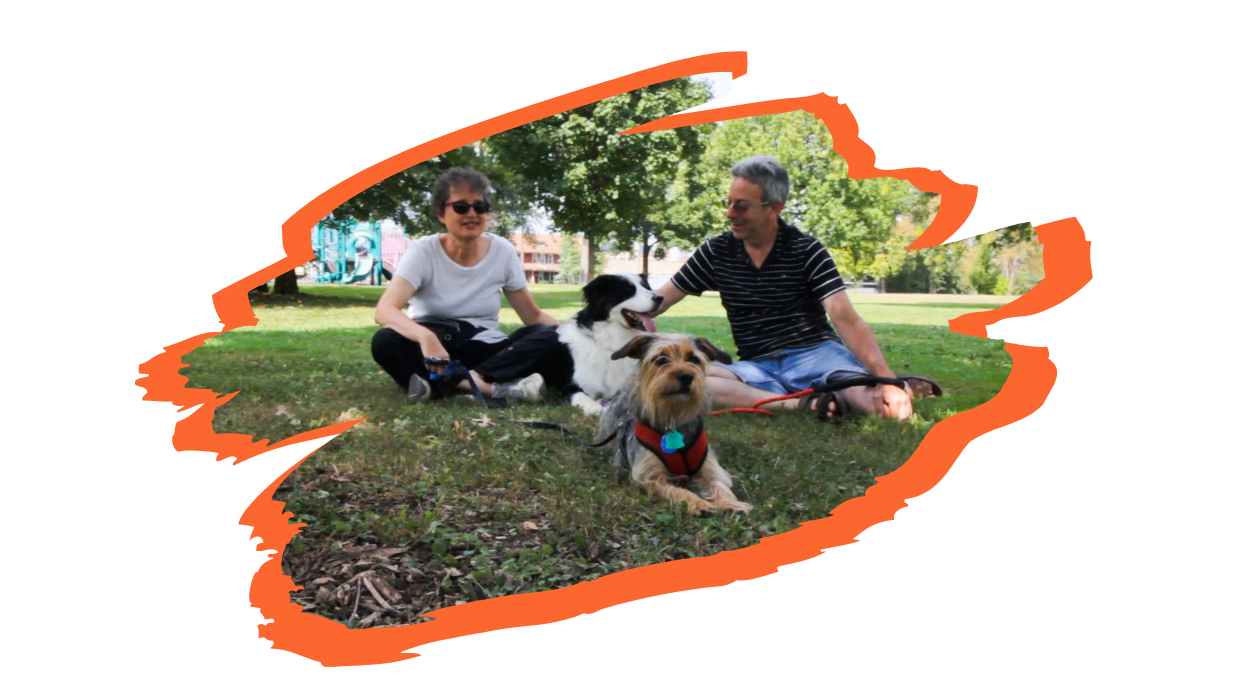 Two spectators sit in a grassy, shady area of Westinghouse park with their two dogs. The spectator on the left is wearing sunglasses and sitting cross-legged. The spectator on the right is wearing prescription glasses with convertible lenses, sitting and petting one of the dogs.