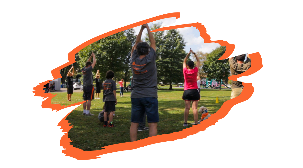 Participants stand in a shaded, grassy area of the park and perform a yoga pose to stretch.